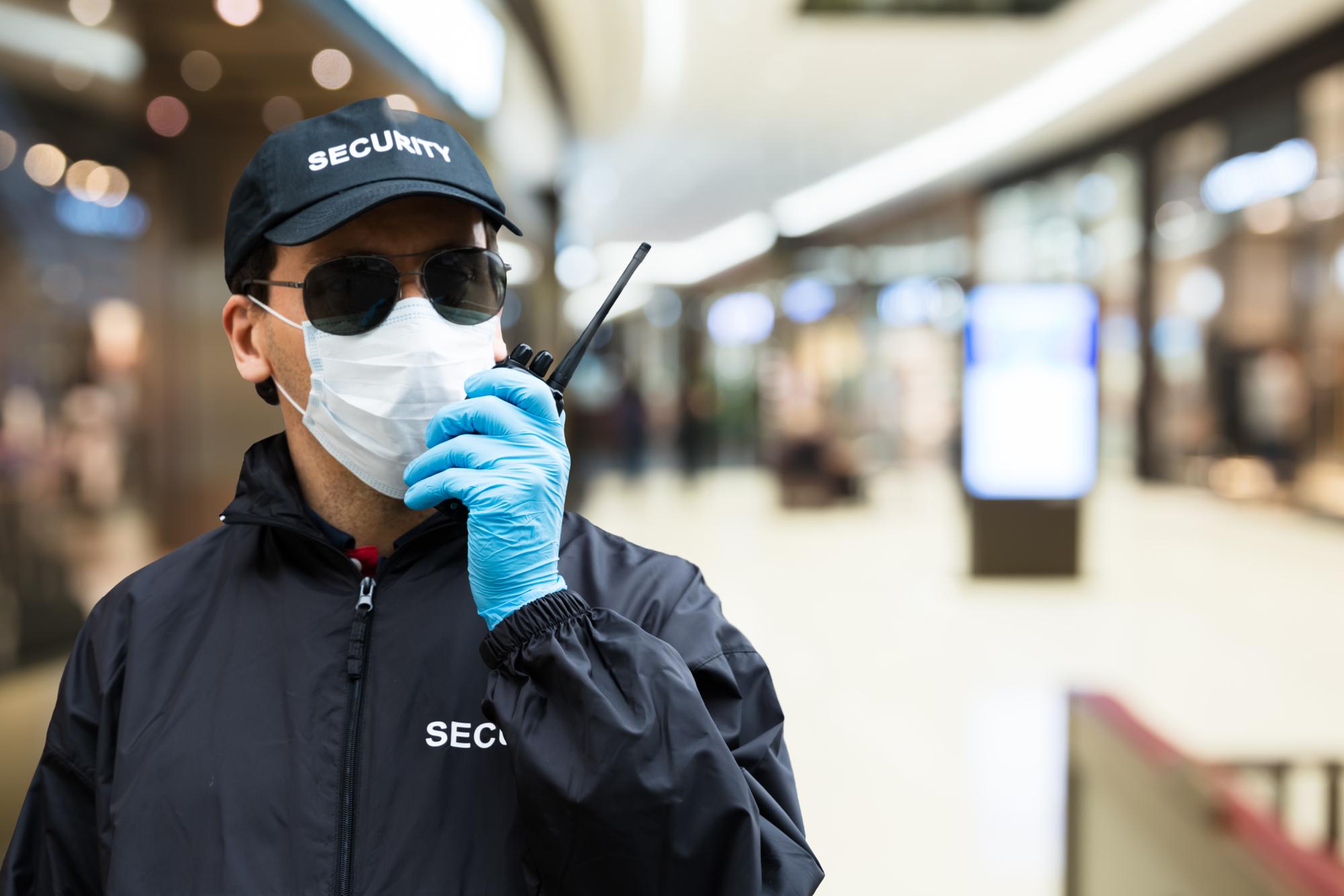 Ochroniarz w maseczce i rękawiczkach rozmawiający przez walkie talkie